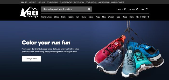 This screenshot of the home page for REI has a black header and navigation bar with white lettering and a white REI logo in the left upper corner, and below it, a page with a dark blue background has a photo of several sneakers hanging by their shoelaces and text in white lettering that reads 'Color your run fun' with an advertisement for running shoes and a white call-to-action button.