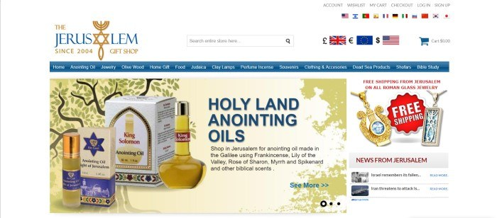 This screenshot of the home page for The Jerusalem Gift Shop has a white background, a blue header, and a golden graphic section with an image of a tree introducing holy anointing oils and including a picture of a few different types of oils, such as King Solomon oil and Light of Jerusalem oil.