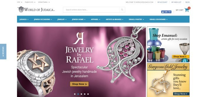 This screenshot of the home page for World of Judaica has a white background, a blue header, and a photo of silver and gold jewelry in front of a purple background.