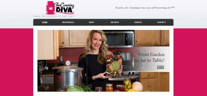 This screenshot of the home page for The Canning Diva has a red textured background, a gray textured header, and a photo of a woman holding a cookbook in a kitchen next to a large pressure cooker.