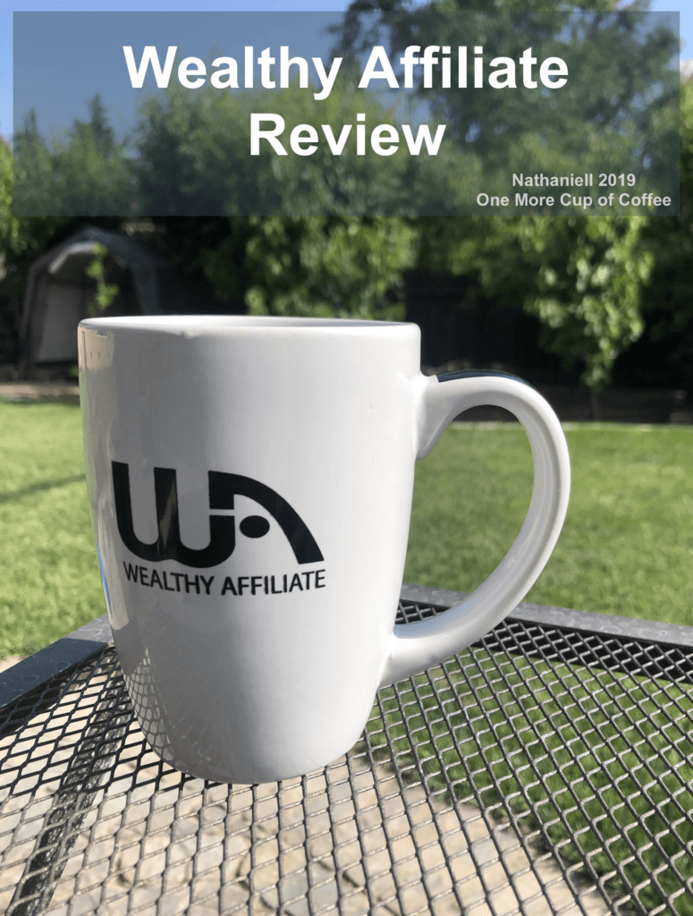 """White mug with black Wealthy Affiliate logo sitting on a wire mesh table with grass and trees in the background and the title text, """"Wealthy Affiliate Review""""."""