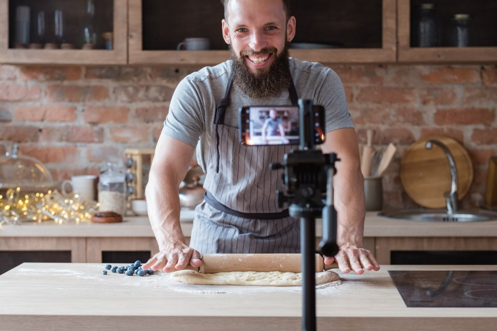 young man with beard filiming a food blog video on a smartphone