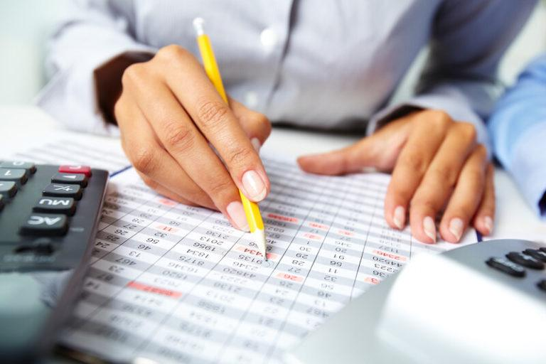 A man's hand rests on an accounting sheet, while the other hand hovers over it, holding a pencil, with two calculators in the foreground, representing the best accounting affiliate programs.