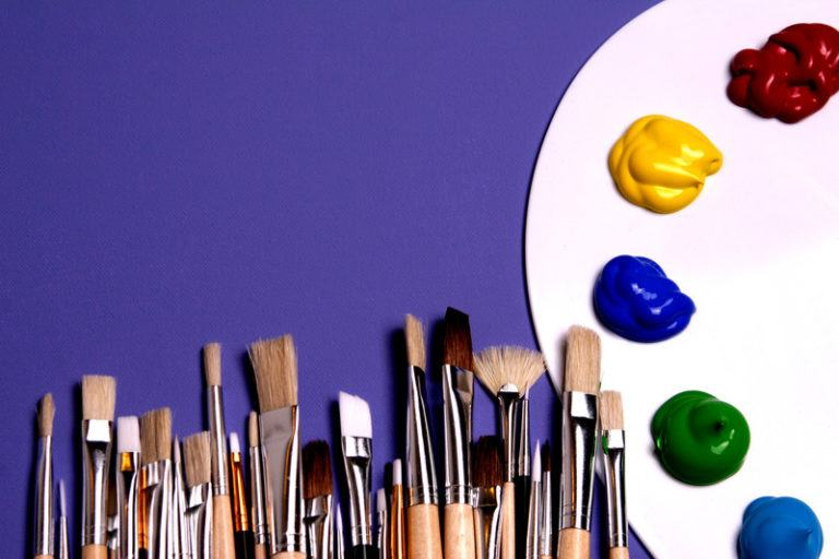This photo has a dark blue background, an artist's palette loaded with colors, and a row of brushes in varying styles and sizes along the bottom edge of the photo, representing the best art supplies affiliate programs.