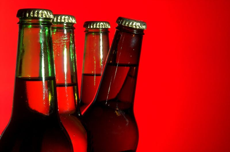 This image has a row of four green-glass beer bottles in front of a red background, with the third bottle leaning forward as if it's peeking out from behind the two bottles in front of it, representing the best home brewing affiliate programs.