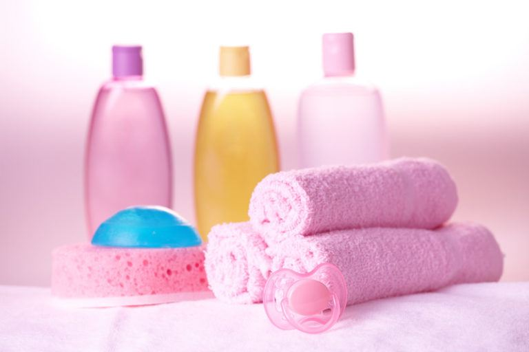 This photo shows a set of baby bath products and a set of three pink wash cloths with a soft pink background, representing the best kids affiliate programs.