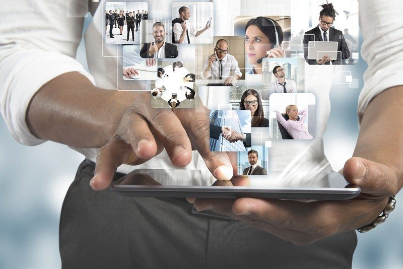 This photo shows a man's hands on a tablet as he manages his team and various projects, representing the best management software affiliate programs.
