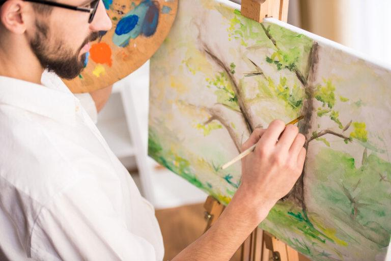 This photo shows a man with dark hair and a beard holding a palette and a paint brush, as if he's about to add more to a painting of some trees on an easel in front of him, representing the best painting affiliate programs.