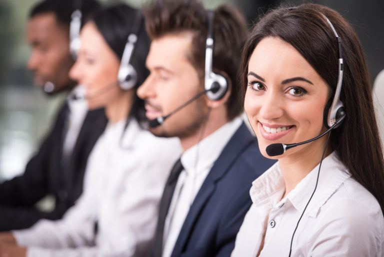 Two men and two women in business clothing and headphones sit at a table with a row of computers, and the woman on the end is looking up and smiling, representing the best telemarketing affiliate programs.