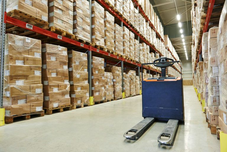 A blue forklift rests in the middle of an aisle between a set of three-story shelves filled with pallets of cardboard boxes, representing the best wholesale affiliate programs.