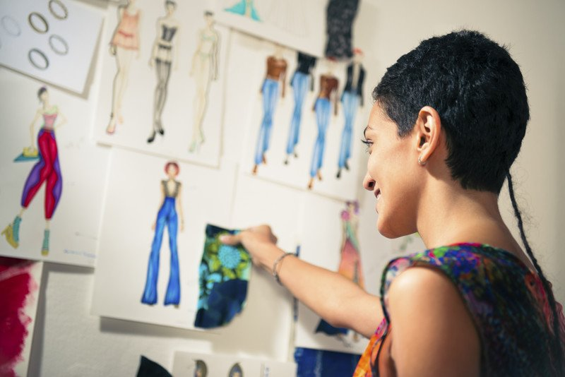 woman looking at fashion drawings on a wall comparing material with a potential sketch to use