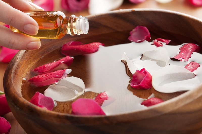 woman putting essential oils into wooden bowl with water and rose petals
