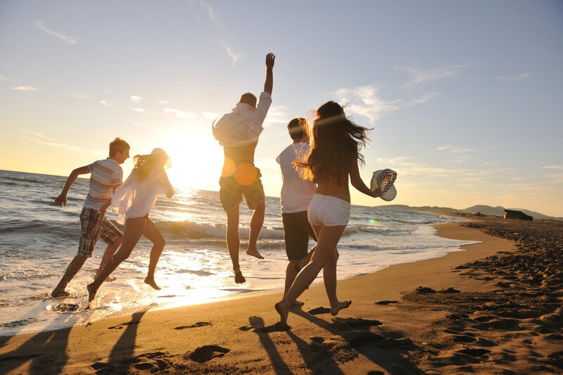 group of five people running on beach with light clothing and cheering