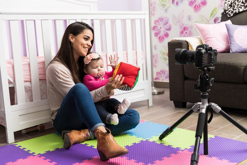 young woman with baby sitting in front of camera with plush toy