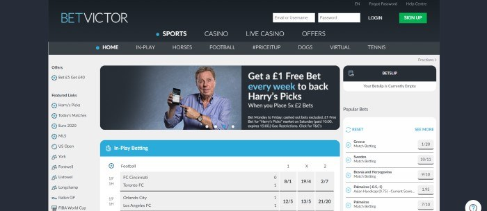 This screenshot of the home page for BetVictor has a black background with a gray, white, and light blue section in the middle with a photo of a man holding up his cell phone as if he's using it to place bets.