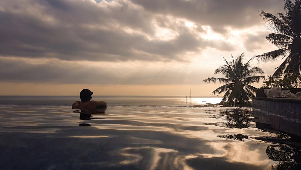 luxury lifestyle man on edge of infinity pool on rooftop