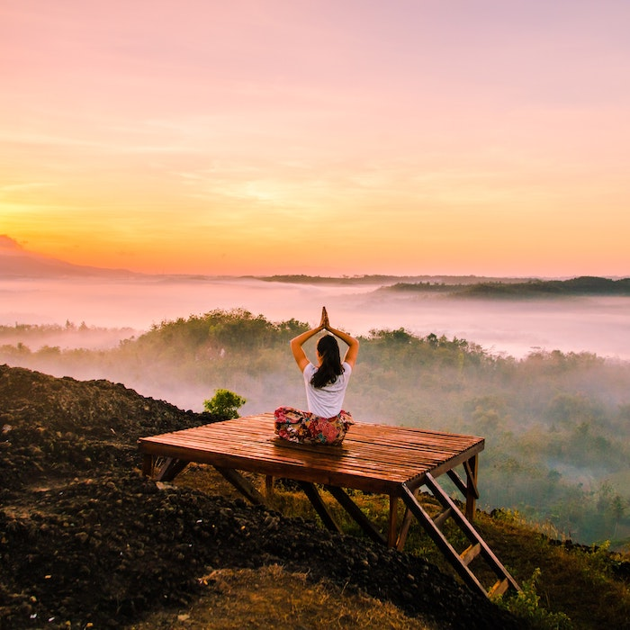 woman doing yoga on mountain deck with sunset in the background