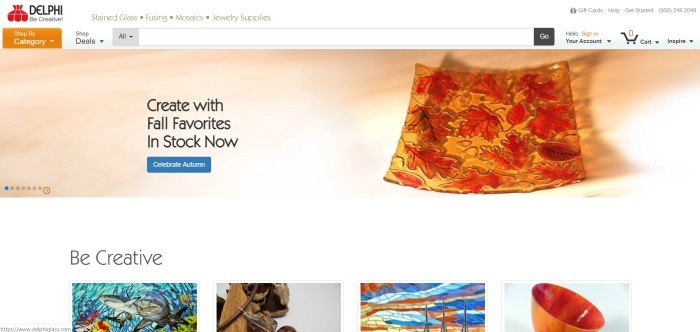 This screenshot of the home page for Delphi Stained Glass shows a piece of glass with fall leaves in it over a tan background with black lettering that reads