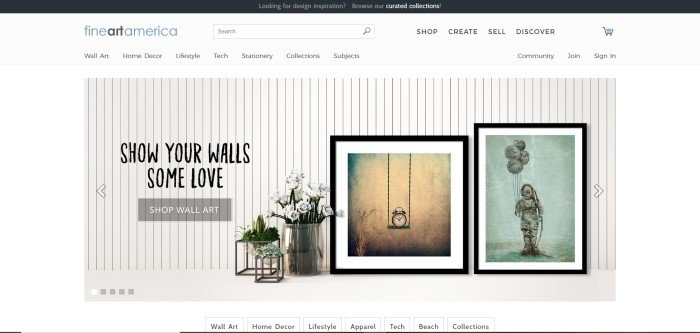 This screenshot of the home page for Fine Art America has a black header, white navigation bar, white background, and a photo of a white wood-paneled wall with several pieces of fine art leaning against it, along with a large silver vase of white flowers and a call-to-action button for shopping for wall art.