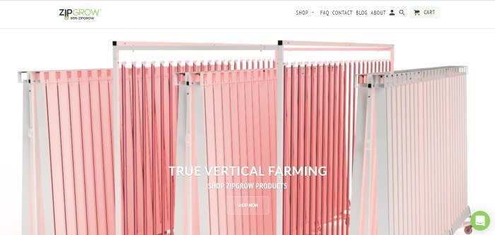This screenshot of the home page for ZipGrow shows a few sections of ZipGrow towers in pink with white frames, behind text in white lettering that reads 'True vertical farming.'