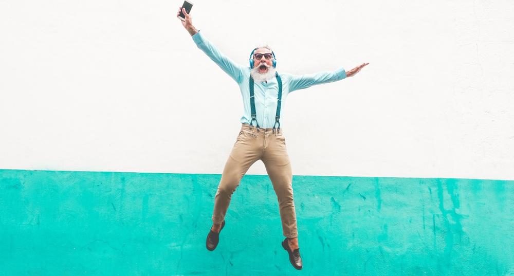 senior man jumping on colorful wall