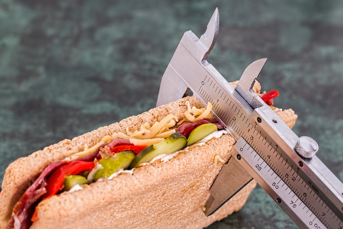 sandwich with bread, pickles, and peppers with body fat measurement tool
