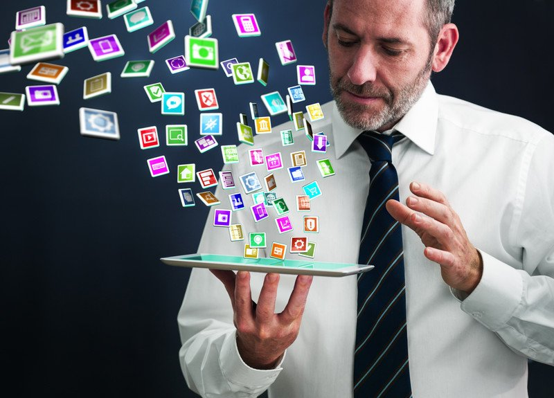 This photo shows a bearded man in business clothes holding a tablet in his hands, while icons for several apps fly in the air around him as if they're emerging from his tablet, representing the best apps affiliate programs.