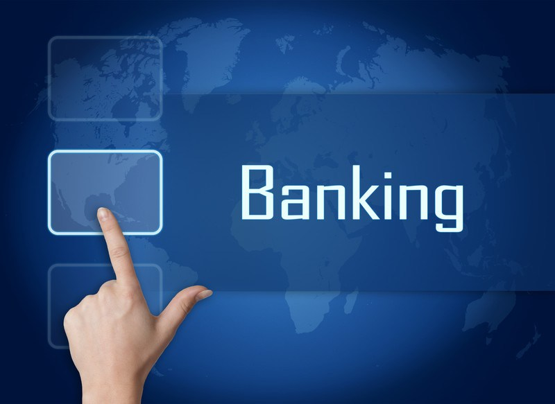 This image has a woman's hand ready to hit a large access button on a screen with the word 'banking' overlaying a blue tinted image of Planet Earth, representing the best banks affiliate programs.