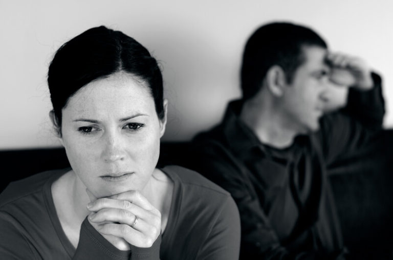 This black and white photo shows a sad or angry man and woman sitting beside each other on a couch, but not looking at each other, representing the best divorce affiliate programs.
