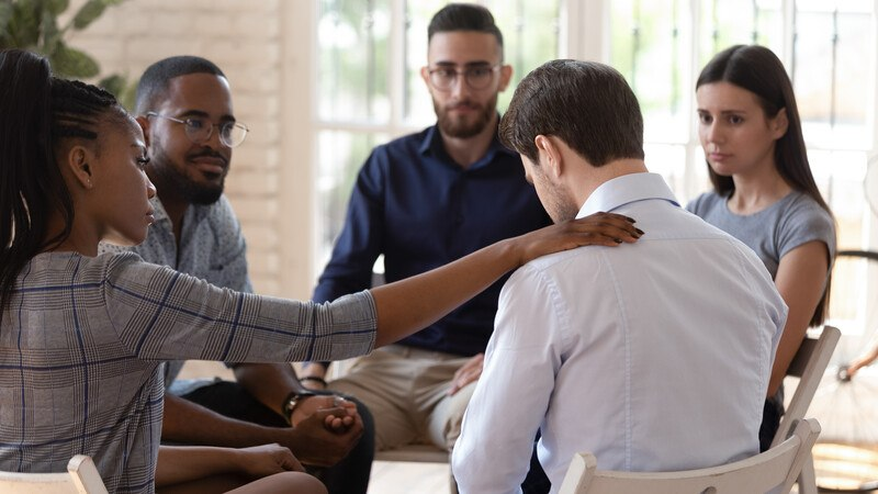 This photo shows a diverse group of four people who appear to be concerned about and talking with a young brown-haired man in a white shirt, who is sitting with his head down, looking at his hands as if he's embarrassed or feeling despair, representing the best drug rehab affiliate programs.