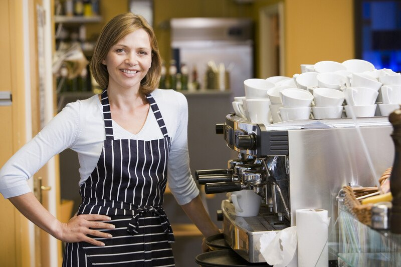 This photo shows a smiling blonde woman in a white shirt and a black and white apron standing in front of an espresso machine and stacks of white espresso cups, representing the best espresso machine affiliate programs.
