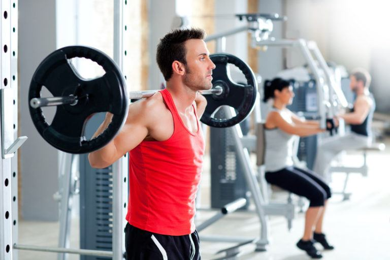 This image shows a man in a red shirt and a woman in a white shirt using workout equipment in what appears to be a gym full of fitness equipment, representing the best fitness equipment affiliate programs.