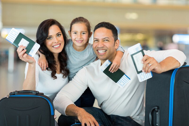 This photo shows a smiling dark-haired woman in a white shirt, a smiling dark-haired man, and a young girl holding passports and boarding passes in the waiting area of an airport, representing the best travelers insurance affiliate programs.