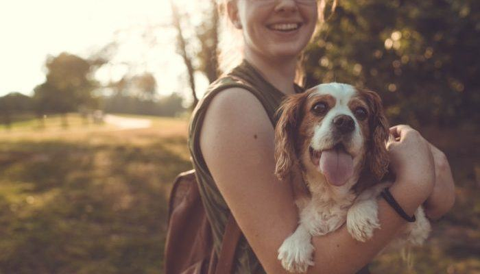 A young woman holding a dog