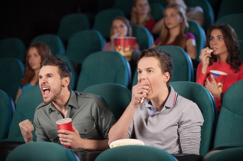 Two men sitting in a theatre watching a movie, with various people behind them