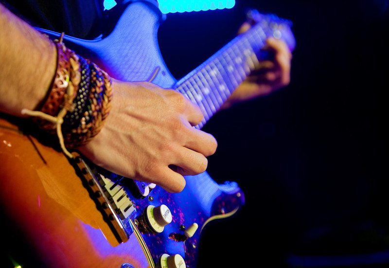 Close up image of a man playing guitar with bracelets on his wrist