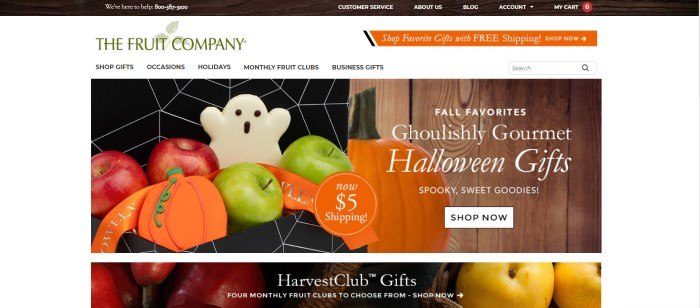 This screenshot of the home page of The Fruit Company has a white background with green and orange elements and black text in the navigation bar, above a photo of a black box with a white spiderweb pattern, which contains green and red apples with white ghost cookies and orange pumpkin cookies, as well as another photo of a pumpkin sitting in front of a rustic wooden wall.