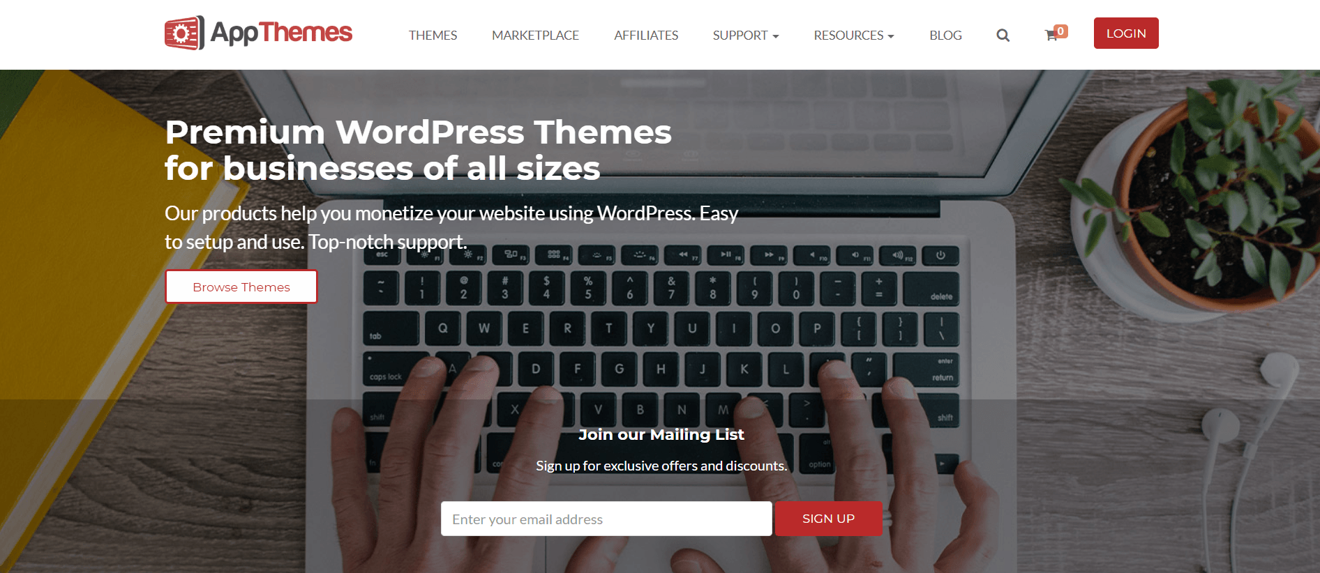 This screenshot of the home page for App Themes has a white navigation bar above an overhead photo of a laptop with hands on the keyboard, behind white lettering announcing premium WordPress themes.