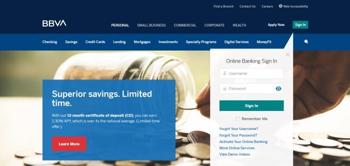 This screenshot of the home page for BBVA Compass has a navy blue header, a lighter blue navigation bar with white wording, a photo of someone putting a coin in a glass jar, and a blue text box announcing superior savings next to a gray window where customers can sign in to the online bank.