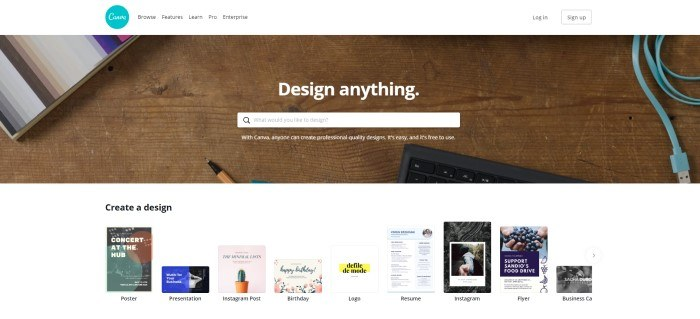 "This screenshot of the home page for Canva shows a wooden desk top with the edge of a black keyboard, the edge of a stack of multi-colored paper, and the tip of a pen, along with white text reading ""Design anything"" and a search bar for getting started."