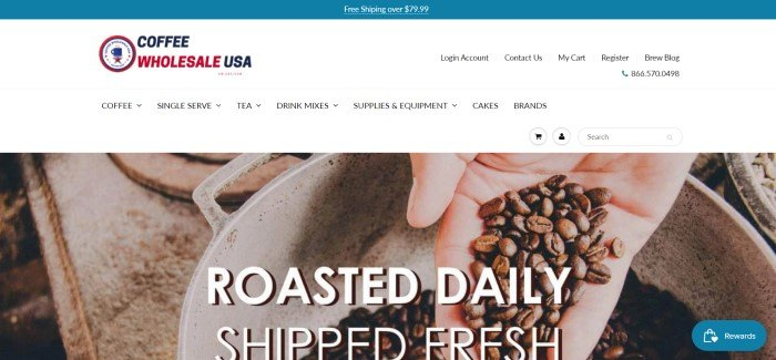 """This screenshot of the home page for Coffee Wholesale USA has a white background with a closeup photo of a hand holding coffee beans, apparently dropping them into a metal bowl, behind white text which reads """"Roasted daily, shipped fresh."""""""
