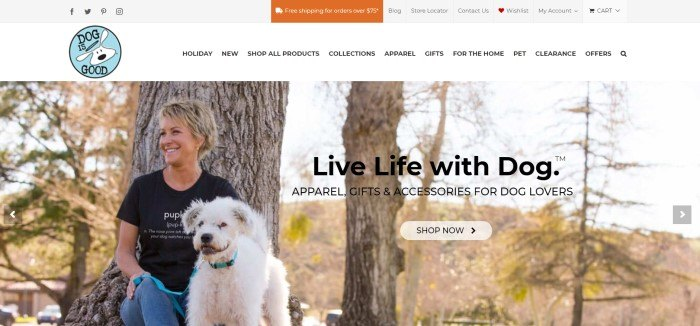 This screenshot of the home page for Dog Is Good has a white background and navigation bar above a large photo of a smiling blonde woman in jeans and a black tee shirt, sitting beside an autumn tree with a large white dog.