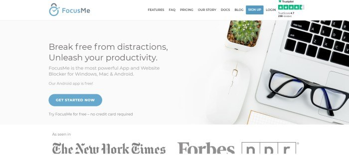This screenshot of the home page for Focus Me has a white navigation bar above a central gray section with an overhead photo of a desk top with a cactus, glasses, and laptop, near black text inviting consumers to break free from distractions with Focus Me.