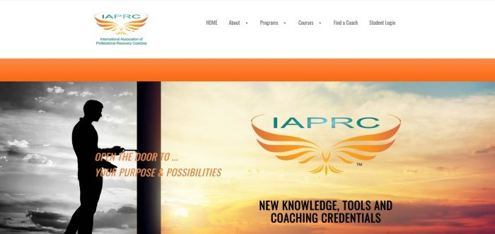 This screenshot of the home page for the International Association Of Professional Recovery Coaches has a white navigation bar, an orange background, and a large image showing the silhouette of a man in front of a black and white sky opening a door that leads to a bright orange and yellow sunrise.