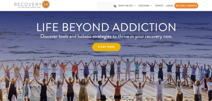 This screenshot of the home page for Recovery 2.0 shows a large circle of people on a beach, smiling, holding hands, and raising their hands in the air at the same time, behind white text that reads
