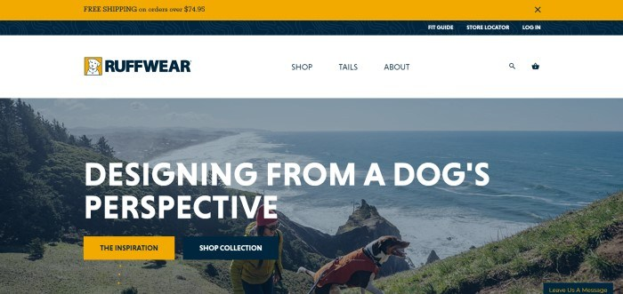 This screenshot of the home page for Ruffwear has a white navigation bar with the Ruffwear logo in it, above a large photo of a woman in an a jacket and beanie hiking along a coastal trail, along with a brown and white dog wearing an orange dog pack.