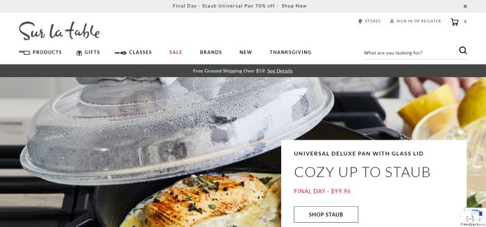 This screenshot of the homepage for Sur La Table has a white navigation bar with black text above a photo of a deluxe pan with cooked chicken inside it, next to a white and black advertisement for the pan.
