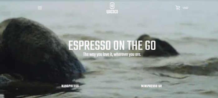 """This screenshot of the home page for Wacaco has a grayish photo of two rocks in the water, behind white text which reads """"Espresso on the go: The way you love it, wherever you are."""""""