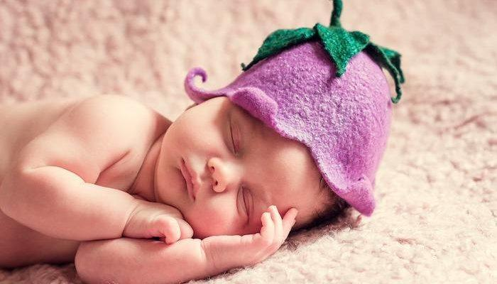 A newborn baby posed with a knitted flower hat
