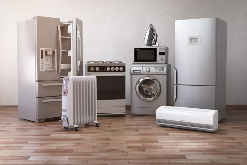 This image showsa row of stainless steel and white appliances, including a refrigerator, a stove, a microwave, a front loading washer, and more in a room with white walls and a brown tile floor, representing the best appliance affiliate programs.
